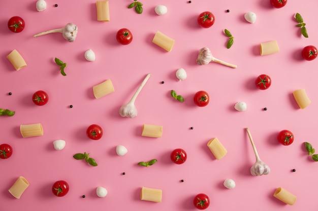 Raw food en ingrediënten concept. ruwe rigatonideeg, tomaten, peperkorrels, basilicum en mozarellakaas op roze achtergrond. italiaanse schotel, vegetarische maaltijd. gezond menu en voedingsconcept