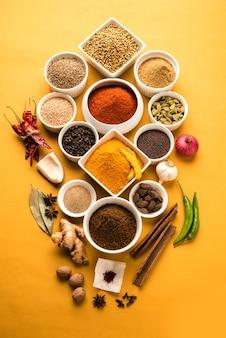 Raw indian spice powder in witte kommen over kleurrijke achtergrond, selectieve focus