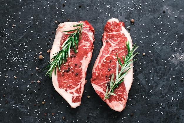 Raw new york lendenstuk biefstuk geïsoleerd op zwart met zeezout en rozemarijn en kruiden.