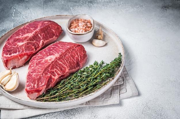 Raw oyster top blade of platte ijzer rosbief vleeslapjes vlees op een plaat met kruiden. bovenaanzicht.