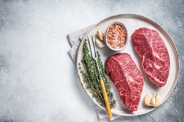 Raw oyster top blade of platte ijzeren rosbief steaks op een bord met kruiden