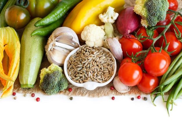 Raw rye grain in een kom en groenten geïsoleerd op wit