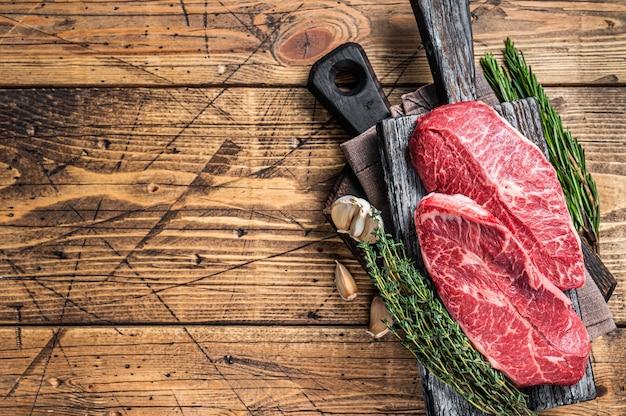 Raw shoulder top blade rundvlees steaks op een houten slager bord met kruiden