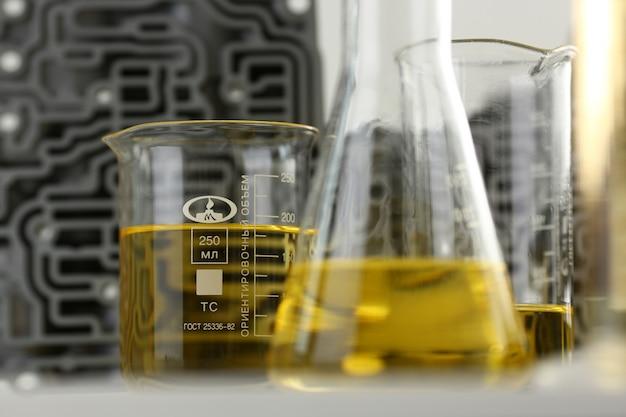 Reageerbuis chemie kolf tegen achtergrond van hydroblok acp met gele vloeibare gezuiverde olie van recycling en smeermiddelen verkoop close-up