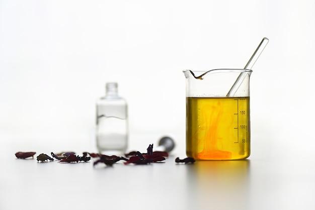 Reageerbuis met etherische oliën van plantenextracten voor natuurlijke cosmetica op een witte achtergrond