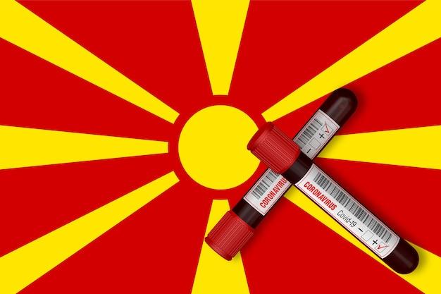 Reageerbuisjes met de inscriptie 2019-ncov op de achtergrond van de vlag van macedonië. 3d-rendering