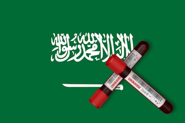 Reageerbuisjes met de inscriptie 2019-ncov op de achtergrond van de vlag van saoedi-arabië. 3d-rendering