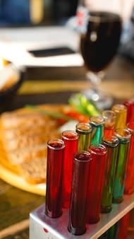 Reageerbuisjes met veelkleurige vloeistof. alcohol in reageerbuizen donkere bar. foto van de bar in lviv, oekraïne