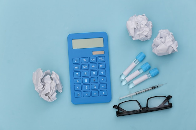 Reageerbuisjes, rekenmachine en spuit met verfrommelde papieren ballen op een blauwe achtergrond. bovenaanzicht
