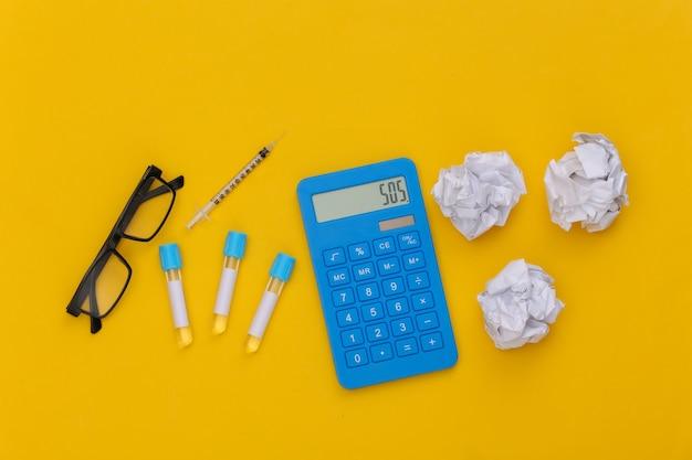 Reageerbuisjes, rekenmachine en spuit met verfrommelde papieren ballen op gele achtergrond. bovenaanzicht
