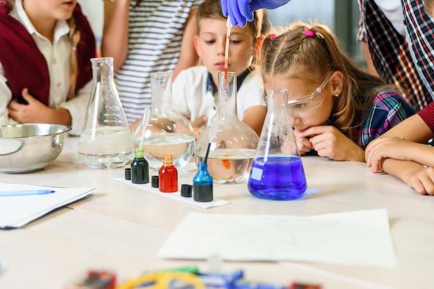 Reageerbuizen met kleurrijke vloeibare stoffen. studie van vloeibare toestanden. groepsschoolleerlingen met reageerbuizen bestuderen chemische vloeistoffen. wetenschap concept. meisjes en jongen die experimenteren met vloeistoffen.