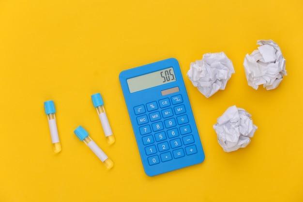 Reageerbuizen, rekenmachine met verfrommelde papieren ballen op gele achtergrond. bovenaanzicht