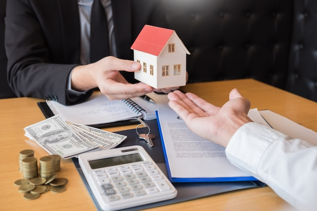 Real estate-ontwikkelaaragent en teken op document die sleutels van nieuw huis geven