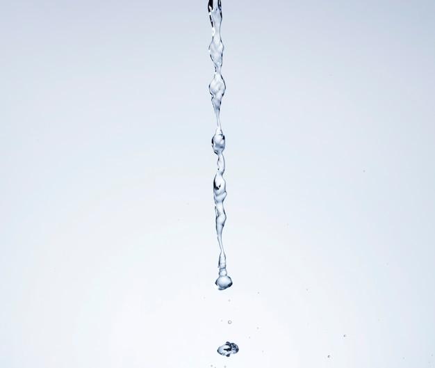 Realistisch water dat op lichte achtergrond wordt gegoten