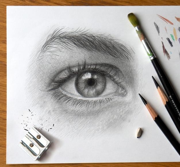 Realistische tekening van een menselijk oog. monochroom hand tekenen. het proces van het werken op het bureaublad van de kunstenaar met kunstmaterialen.