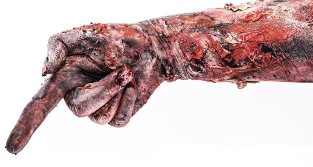 Realistische zombie of ondode hand wijzend in een richting met wijsvinger, geïsoleerd wit oppervlak.