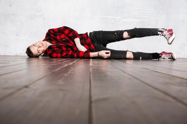 Rebellen man in geruite overhemd op de vloer liggen