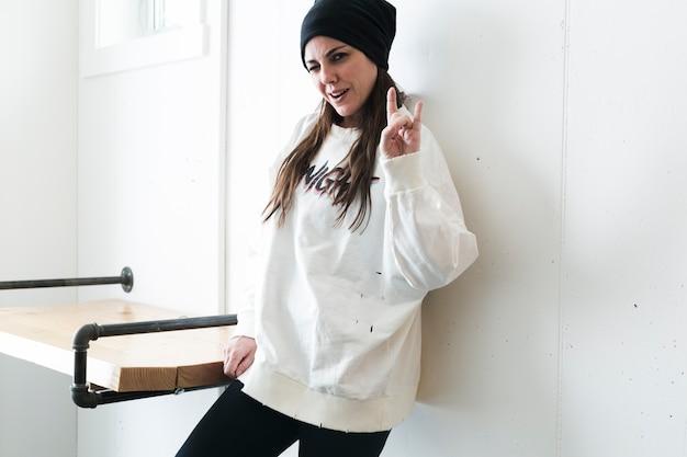 Rebellenmeisje in hoed die gebaar toont bij camera