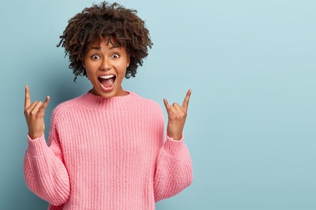 Rebelse emotionele vrouw geniet van muziekfestival, coole liedjes, maakt rock n roll-gebaar, roept luid uit, rockt en voelt cool