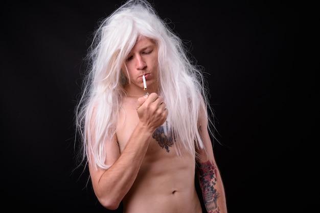 Rebelse man als punkrocker met pruik shirtless tegen zwart
