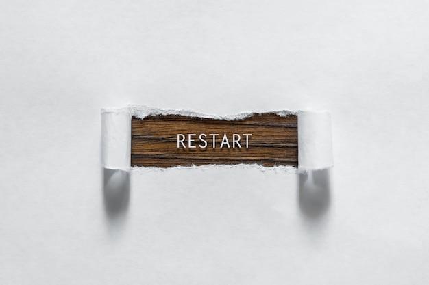 Reboot - een inscriptie in het gescheurde wit papier