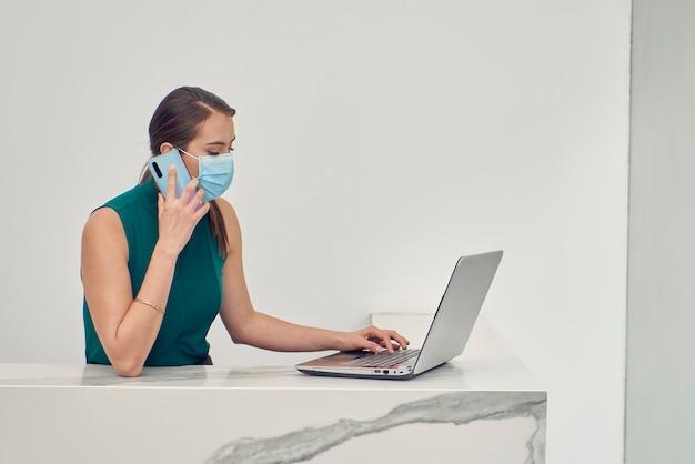 Recepcionista latina con cubrebocas hablando por telefono mientras trabaja en su laptop