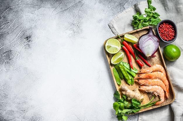 Recept en ingrediënten tom kha gai. thaise galangal kippensoep in kokosmelk. grijze achtergrond. bovenaanzicht. kopieer ruimte