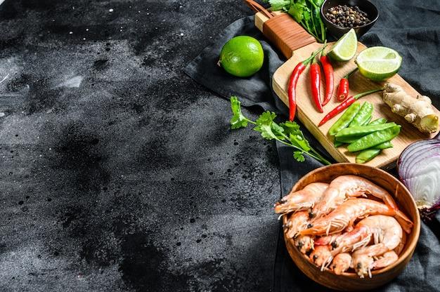 Recept en ingrediënten tom kha gai. thaise galangal kippensoep in kokosmelk. zwart oppervlak. bovenaanzicht. kopieer ruimte