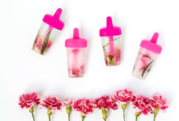 Recept van jeugd, gezichtsverzorging, ijsblokjes in de vorm van ijs met kruiden en anjer roze bloemen op wit wordt geïsoleerd