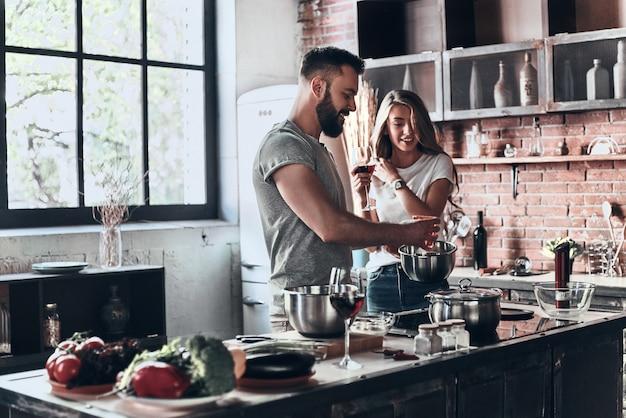 Recept vereist veel liefde. mooi jong stel dat samen een gezonde maaltijd bereidt terwijl ze thuis vrije tijd doorbrengt