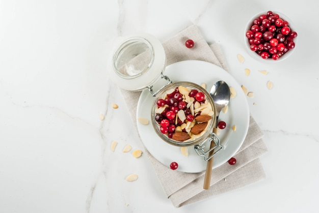 Recept voor een gezond winterontbijt, ideeën voor kerstochtend. overnachting havermout met amandelen, veenbessen, suiker. . copyspace bovenaanzicht