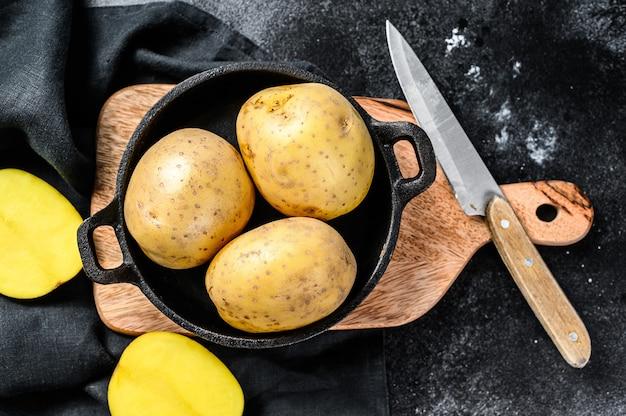 Recept voor gebakken aardappelen, biologische gele aardappelen in een pan. zwarte achtergrond. bovenaanzicht.