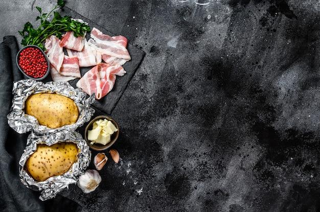 Recept voor het koken van gebakken aardappelen. ingrediënten spek, boter, peterselie en kaas. bovenaanzicht. kopieer ruimte