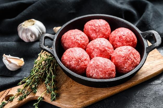 Recept voor het koken van gehaktballetjes van gehakt in een pan. zwarte achtergrond. bovenaanzicht