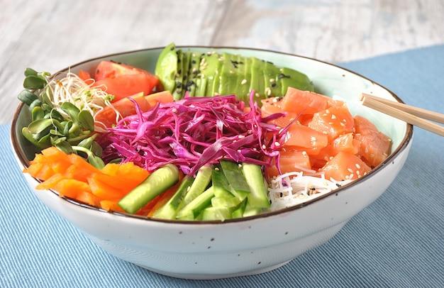 Recept voor verse zeevruchten. biologisch voedsel. verse zalmpoke kom met kristalnoedels, verse rode kool, avocado, kerstomaatjes food concept zakje