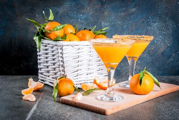 Recepten en ideeën van winterfruitcocktails, tangerine martini margarita met verse mandarijnen in de mand, op donkere achtergrond, kopie ruimte