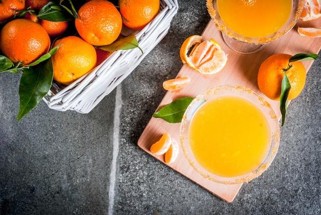 Recepten en ideeën van winterfruitcocktails, tangerine martini margarita met verse mandarijnen, op donkere achtergrond, kopie ruimte bovenaanzicht