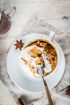 Recepten met pompoenen, fast food, magnetron maaltijd. pittige pompoentaart in mok, met slagroom, ijs, kaneel, anijs. op witte houten tafel, met een kop warme chocolademelk. kopieer ruimte bovenaanzicht