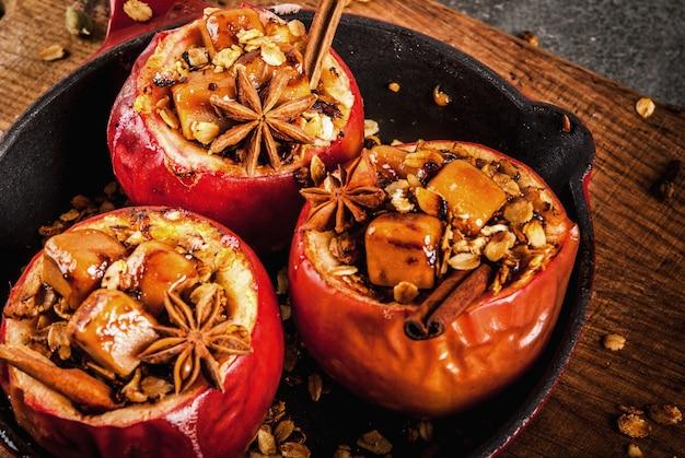 Recepten voor herfstvoedsel gebakken appels gevuld met granola toffee en kruiden in een koekenpan