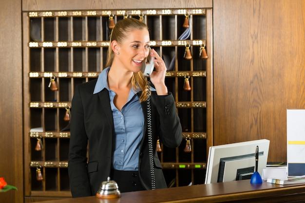 Receptie van hotel, baliemedewerker die een oproep beantwoordt