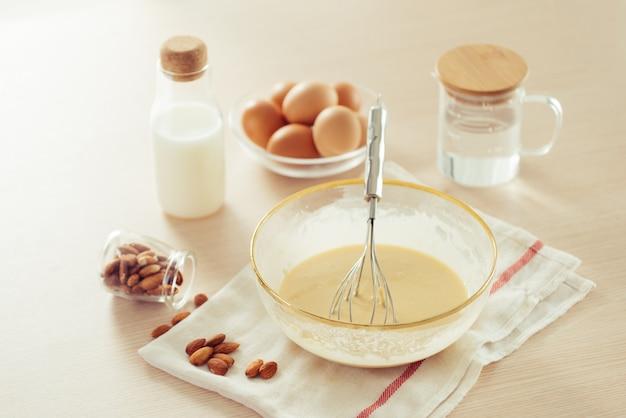 Receptingrediënten: eieren, bloem, melk, amandelen, banaan op een witte ondergrond