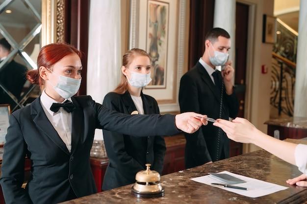 Receptioniste aan balie in hotel met medische maskers
