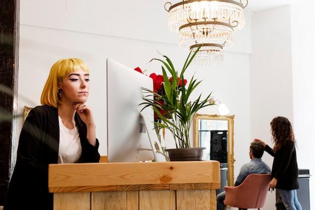 Receptioniste bij computer in schoonheidssalon
