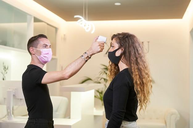 Receptioniste die een infraroodthermometer gebruikt om de temperatuur op te nemen. vrouwelijke patiënt medische masker dragen in onderzoekskamer bij kliniek.