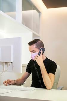 Receptioniste die werkt bij de receptie van de tandheelkundige, gynaecologische of esthetische kliniek. de receptioniste neemt een telefoontje aan. medisch concept. verticale foto.