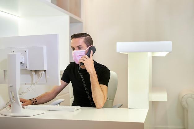 Receptioniste die werkt bij de receptie van de tandheelkundige, gynaecologische of esthetische kliniek. de receptioniste neemt een telefoontje aan. medisch concept.