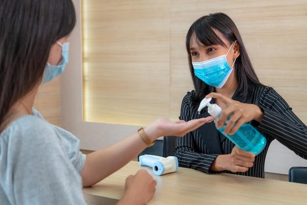 Receptioniste en gast dragen gezichtsmasker bij de receptie tijdens een gesprek op kantoor of in het ziekenhuis