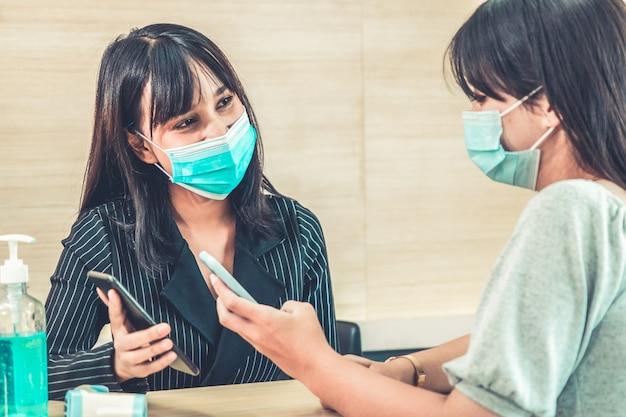 Receptioniste en gast met gezichtsmasker bij receptie.