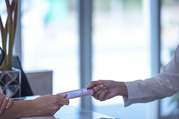 Receptioniste overhandigt een paspoort aan een toerist bij de receptie en receptie van een hostel