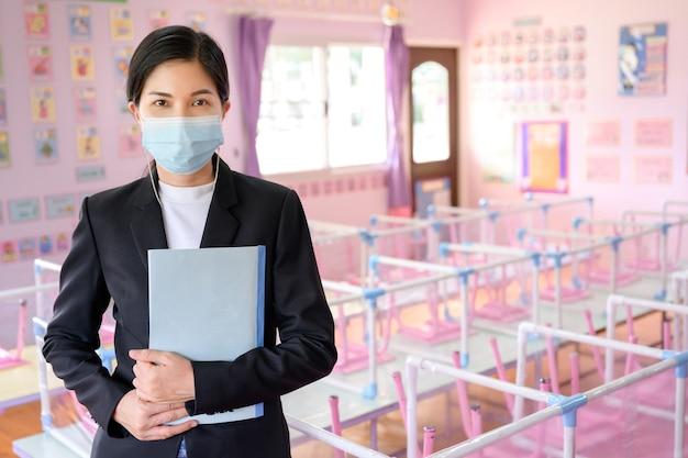 Recesschool voor kinderen en jonge aziatische leraren dragen maskers om de verspreiding van covid 19 in een klaslokaal zonder leerlingen te voorkomen.